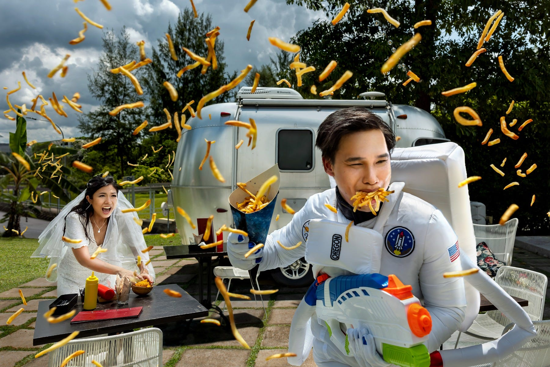 Wedding couple throws French fries in a dramatic pre-wedding photoshoot.]